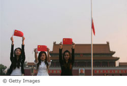 Three girls stand in Tiananmen Square on a day of rememberence of the 1989 event
