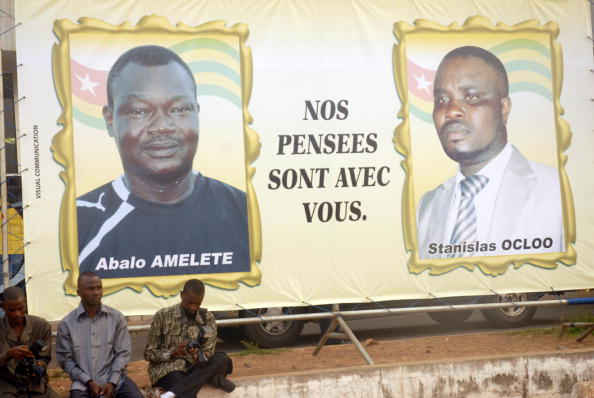 Photographers sit beside a billboard showing portraits of the victims of an attack on the bus carrying the Togo national football team, ahead of a ceremony in Lome on January 15, 2010. EMILE KOUTON/AFP/Getty Images