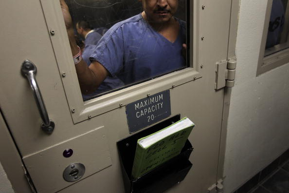 An immigrant stands in a holding cell at the U.S. Immigration and Customs Enforcement (ICE) detention facility for illegal immigrants on July 30, 2010 in Florence, Arizona. (Photo by John Moore/Getty Images)