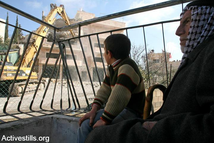 Grandfather and grandchild watch home in Sur Baher east Jerusalem being demolished by CAT machinery.  Keren Manor/ActiveStills.org