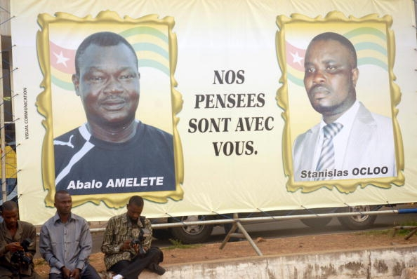Billboard showing portraits of the victims of an attack on the bus carrying the Togo national football team.