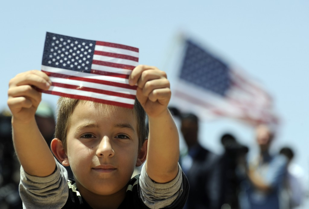 A boys shows a U.S. flag as President Barack Obama speaks about immigration at the Chamizal National Memorial in El Paso, Texas, in 2011. (Photo credit: Jewel Samad/AFP/Getty Images)