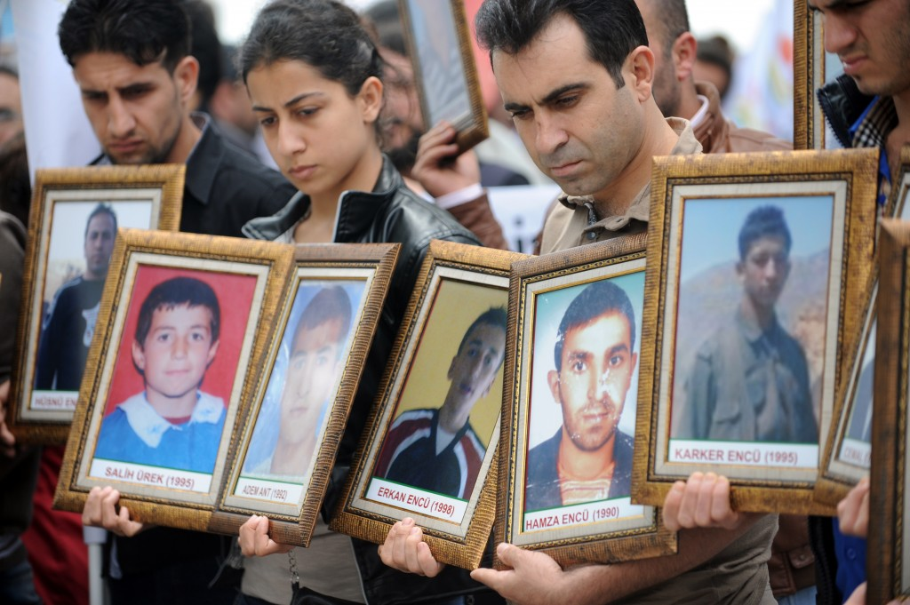 Kurdish people hold pictures of victims killed in a Turkish air raid during a demonstration on May 26, 2012, in Istanbul. (Photo credit BULENT KILIC/AFP/GettyImages)