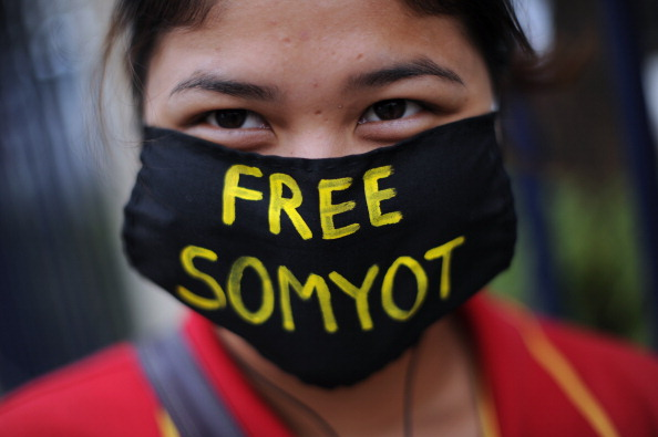 A Thai activist wears a face mask carrying a message reading 'Free Somyot' as she joins a protest outside the Criminal Court in Bangkok on January 25, 2013.      (Photo credit:  CHRISTOPHE ARCHAMBAULT/AFP/Getty Images)
