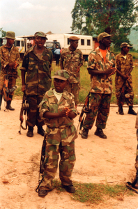 Child soldier with adults, Sanghe, Democratic Republic of Congo, June 2002.