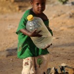A Malian girl carries a water can she just partially filled at a water pump in northern Mali's city of Gao (Photo credit should read Pascal Guyot/AFP/Getty Images).