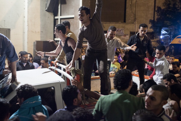 Egyptian protesters cheer as they enter the grounds of the St Mark's Cathedral in Abasseyya during clashes with Egyptian riot police on April 7, 2013 in Cairo, Egypt (Photo Credit: Ed Giles/Getty Images).