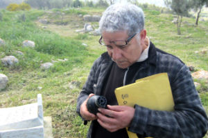 Lamri Chirouf inspects an Israeli tear gas canister in Budrus cemetery (Photo Credit: Amnesty International).