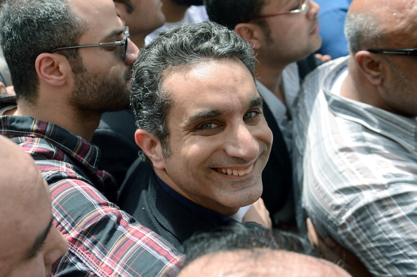 Egyptian satirist and television host Bassem Youssef surrounded by his supporters upon his arrival at the public prosecutor's office in the high court in Cairo.  Egypt's public prosecutor ordered the arrest of popular satirist Youssef over alleged insults to Islam and to President Mohamed Morsi, in the latest clampdown on critical media (Photo Credit: Khaled Desouki/AFP/Getty Images).