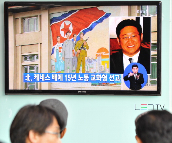 "Passersby watch a television broadcast in Seoul showing a picture of Kenneth Bae, a Korean-American tour operator detained in North Korea, and sentenced to 15 years' hard labor for ""hostile acts"" (Photo Credit: Kim Jae-Hwan/AFP/Getty Images)."