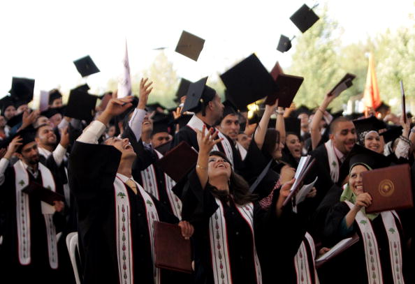 Palestinian students celebrate during their graduation ceremony at Birzeit University. Birzeit is the university of choice for Azza, Suhair and Loujain. However, like many Palestinian students, they are restricted from attending because the university is in the West Bank and they live in Gaza (Photo Credit: Abbas Momani/AFP/Getty Images).