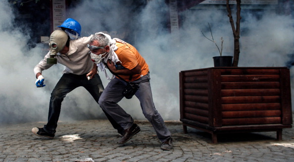 Demonstrators try to escape from riot police on June 11, 2013 on Taksim square in Istanbul. Riot police fired tear gas and rubber bullets to clear protesters as Turkish Prime Minister Recep Tayyip Erdogan warned he would show 'no more tolerance' for the unrelenting mass demonstrations against his Islamic-rooted government (Photo Credit: Angelos Tzortzinis/AFP/Getty Images).