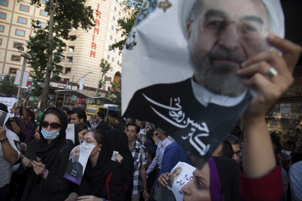 People hold campaign posters of Iranian presidential candidate, Hassan Rowhani in the streets during a presidential election rally on June 11, 2013 in Tehran, Iran (Photo Credit: Majid Saeedi/Getty Images).