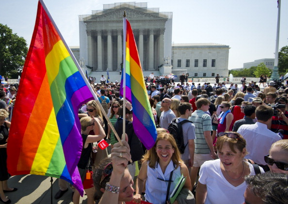 Gay rights activists gather outside the U.S. Supreme Court building in Washington, D.C. Today, the Supreme Court struck down a controversial federal law that defines marriage as a union between a man and a woman, in a major victory for supporters of same-sex marriage (Photo Credit: Mladen Antonov/AFP/Getty Images).