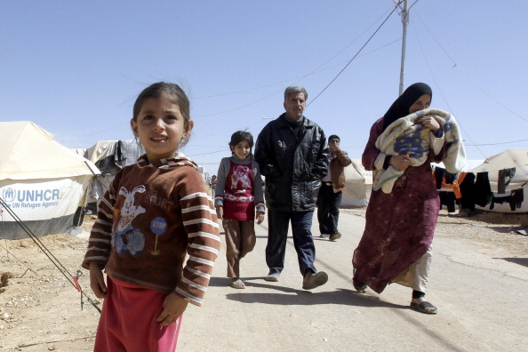 A Syrian family walk amid tents at the Za'atari refugee camp (Photo Credit: Khalil Mazraawi/AFP/Getty Images).