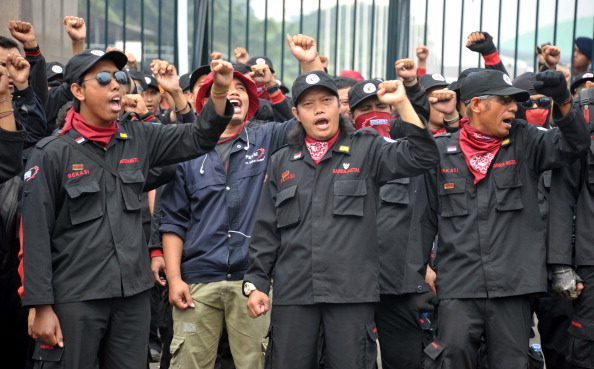 Indonesian workers shout slogans during a protest in front of Parliament building in Jakarta as lawmakers attend the plenary session to pass the mass organization bill. The workers unions vowed to appeal the controversial restriction to Indonesia's freedom of assembly laws in the Constitutional Court (Photo Credit: Bay Ismoyo/AFP/Getty Images).