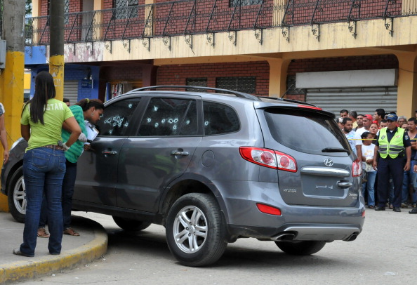 Investigations personnel inspect the car of Honduran Judge Mireya Efigenia Mendoza Pena, where she was found shot dead on July 24, 2013. 64 law professionals including Mendoza have been killed in Honduras since January 2010. (Photo Credit: STR/AFP/Getty Images).