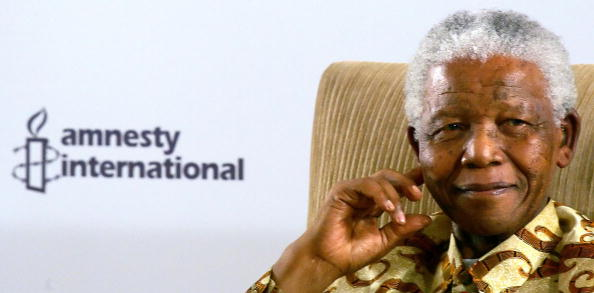 "Nelson Mandela poses after receiving the Amnesty International ""Ambassador of Conscience"" Award in Johannesburg on November 1, 2006 (Photo Credit: Alexander Joe/AFP/Getty Images)."