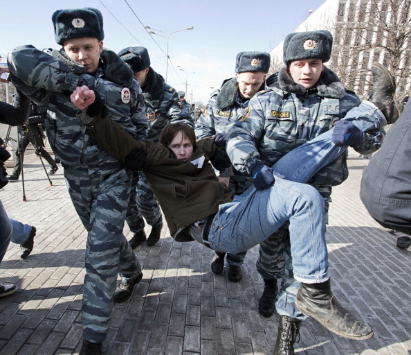 Policemen detain an opposition supporter taking part in a picketing calling for the release of the two jailed members the Pussy Riot (Photo Credit: Evgeny Feldman/AFP/Getty Images).