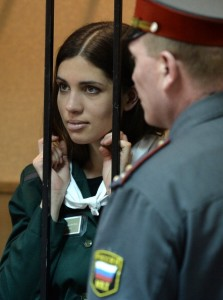 One of the jailed members of 'Pussy Riot,' Nadezhda Tolokonnikova, looks on while standing in the defendant's cage in a court in the town of Zubova Polyana (Photo Credit: Maksim Blinov/AFP/Getty Images).