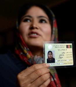 An Afghan woman displays her voter registration card at a voter registration center (Photo Credit: Shah Marai/AFP/Getty Images).