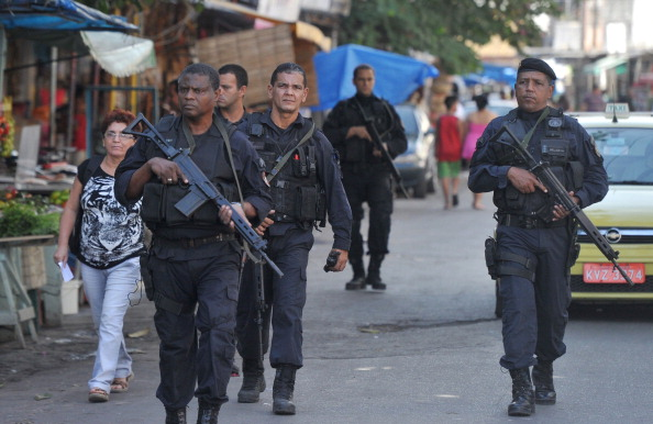 Officers with a special operations force known as BOPE patrol the streets of the violence-plagued Mare complex. Brazilian authorities have stepped up a pacification drive, in part to prepare for Rio de Janeiro to host the World Cup and the 2016 Summer Olympics (Photo Credit: Christophe Simon/AFP/Getty Images).