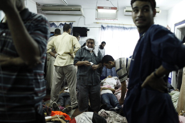 A supporter of deposed Egyptian President Mohammed Morsi stands among the bodies of dead pro-Morsi protesters on the floor of the Rabaa al-Adaweya Medical Centre in Cairo, Egypt (Photo Credit: Ed Giles/Getty Images).