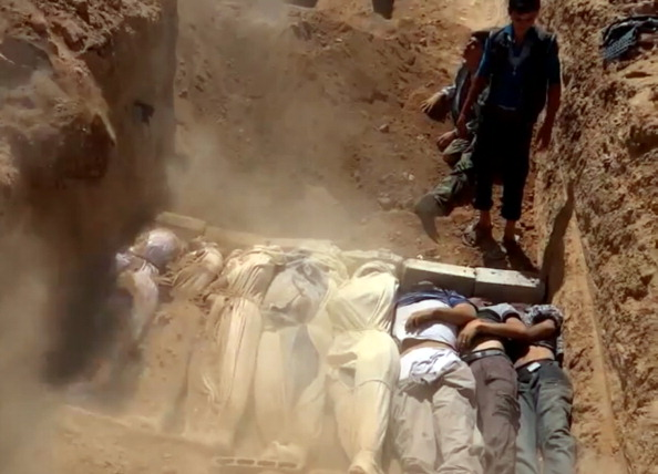 Image from a civilian-uploaded YouTube video allegedly shows a mass grave of victims Syrian rebels claim were killed in a toxic gas attack by pro-government forces on the outskirts of Damascus. The allegation of chemical weapons being used in the heavily-populated areas came on the second day of a mission to Syria by U.N. inspectors. The claim could not be independently verified and was vehemently denied by the Syrian authorities, who said it was intended to hinder the mission of U.N. chemical weapons inspectors (Photo Credit: DSK/AFP/Getty Images).