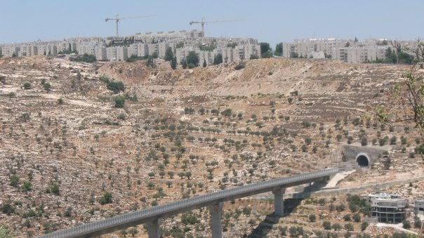 An 'Israeli only' by-pass road that links Israeli settlements in the occupied West Bank, sitting below an Israeli settlement outside of Jerusalem (Photo Credit:  Edith Garwood).