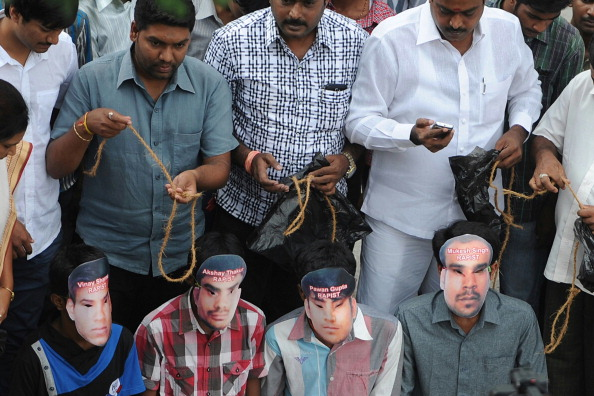 Youths, wearing masks of the four convicted rapists, enact a mock execution following the sentencing in New Delhi of four men convicted of rape and murder (Photo Credit: Manjunath Kiran/AFP/Getty Images).