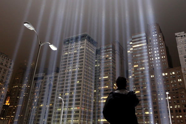 A worker looks up at beams of the Tribute in Lights ahead of the tenth anniversary of the September 11 attacks on September 7, 2011 in New York City. The Tribute in Light is comprised of 88,7000 watt searchlights that beam into the sky near the site of the World Trade Center in remembrance of the September 11 attacks (Photo Credit: Justin Sullivan/Getty Images).