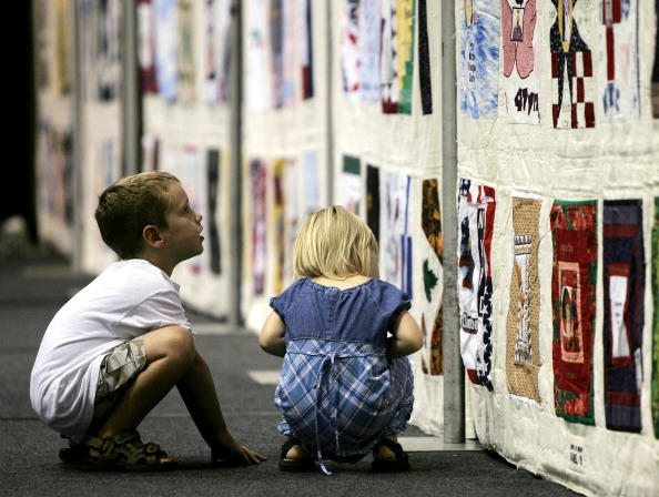 Chris Malone and his sister Samantha view sections of the 16,000 square foot United in Memory 9/11 Victims Memorial Quilt at George Washington University September 8, 2005 in Washington, D.C. (Photo Credit: Win McNamee via Getty Images).