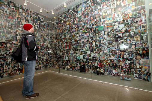 Man looking at pictures and personal items of September 11th victims at the Tribute WTC Visitor's Center, New York City (Photo Credit: Steven Greaves via Getty Images).