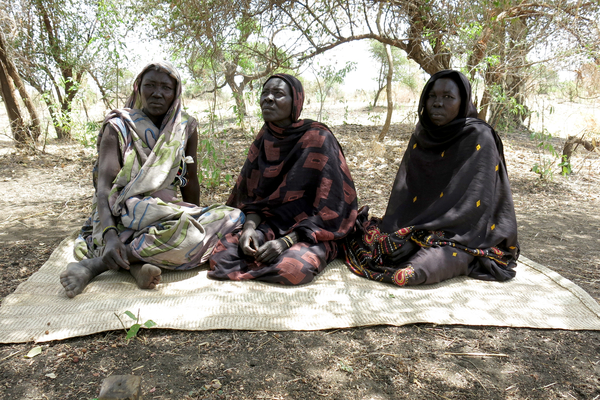 Three displaced Sudanese women finding refuge under a tree (Photo Credit: Jean-Baptiste Gallopin for Amnesty International).