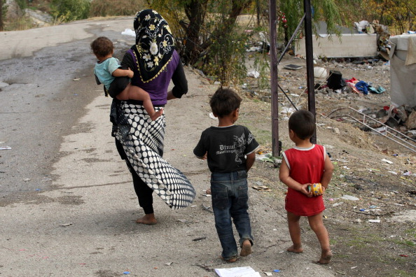 A Syrian refugee woman and children walk near their makeshift tents (Photo Credit: Adem Altan/AFP/Getty Images).