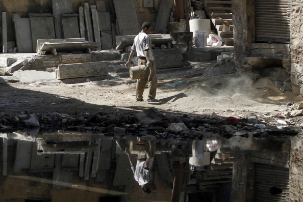 An Egyptian man works at a Cairo slum. Forty percent of Egyptians live on two dollars a day or less, according to the World Bank. Unemployment is rife among the young, forcing many to put off marriage and children until well into their 30s. (Photo Credit: Mahmud Hams/AFP/Getty Images).