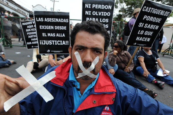 A journalist with his mouth taped takes part in a protest against the murder of colleagues in Tegucigalpa (Photo Credit: Orlando Sierra/AFP/Getty Images).