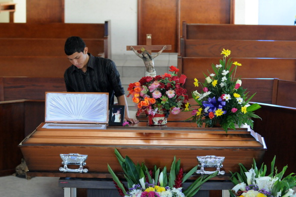 A young man stands beside the coffin of Honduran journalist Saira Fabiola Almendarez. According to the Honduran Human Right Defense Committee, 18 journalists have been murdered in the last three years in the country (Photo Credit: Orlando Sierra/AFP/Getty Images).