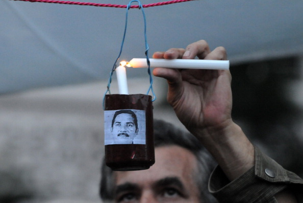 A man lights a candle during a vigil in memory of over 20 journalists killed in Honduras in the last three years (Photo Credit: Orlando Sierra/AFP/Getty Images).