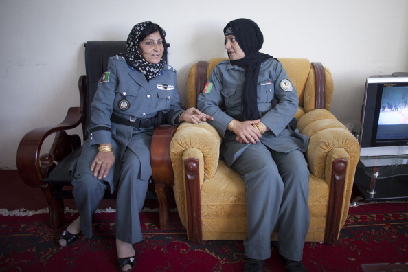 Lieutenant Islam Bibi Helmand's top female police officer (R) talking to a colleague on March 8, 2013. Known as the most senior female police officer in Afghanistan's Helmand province, Bibi was shot dead on July 4, 2013 by unknown gunmen while being driven to work. The attack is seen as part of a series violence against top women officials (Photo Credit: Majid Saeedi/Getty Images).