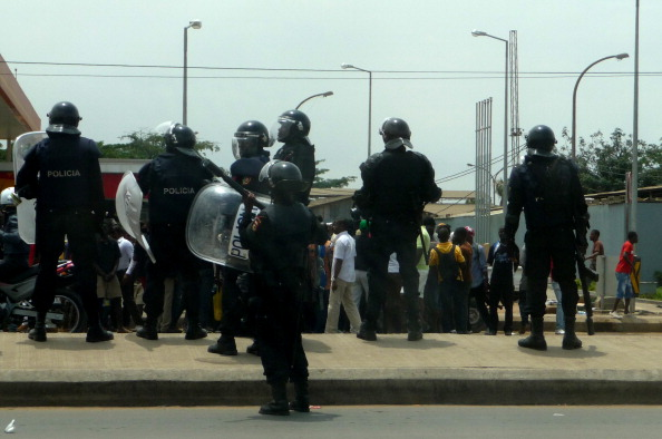 Angolan riot policemen stand in front of hundreds of demonstrators protesting against the killings of two young opposition activists in Luanda (Photo Credit: Estelle Maussion/AFP/Getty Images).