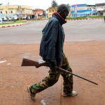 A man holds a rifle as he walks in a street of Bangui, Central African Republic (Photo Credit: Sia Kambou/AFP/Getty Images).