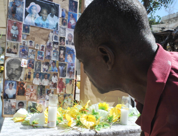 A man pays his respects at a makeshift memorial for victims of the January 12, 2010 Haiti earthquake. An estimated 250,000 people were killed in the January 12, 2010 earthquake. Hundreds of thousands are still living rough in squalid makeshift camps (Photo Credit: Thony Belizaire/AFP/Getty Images).