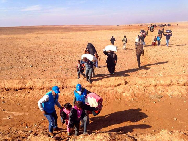 Syrian women, men and children, crossing the border to Jordan. Forced to leave everything behind, except what they can carry, they're running for their lives (Photo Credit: Sweaters for Syria).