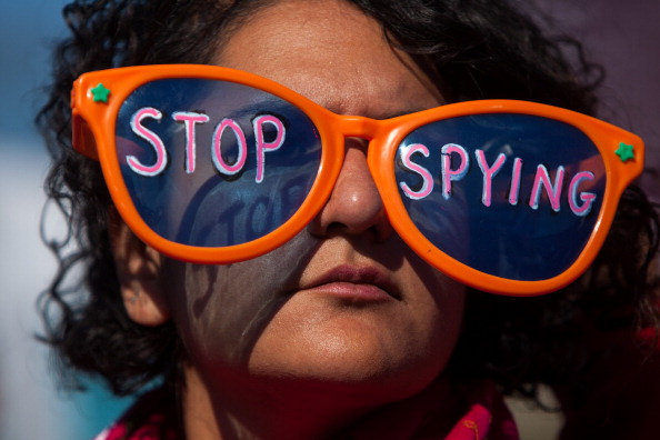 A woman listens to speakers during the Stop Watching Us Rally protesting surveillance by the U.S. National Security Agency (Photo Credit: Allison Shelley/Getty Images).