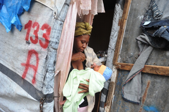 A woman holds her child at a camp for earthquake victims (Photo Credit: Louis-Joseph Olivier/AFP/Getty Images).