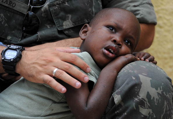A Brazilian soldier of the MINUSTAH force hugs an Haitian child orphaned by the 2010 earthquake (Photo Credit: Vanderlei Almeida/AFP/Getty Images).