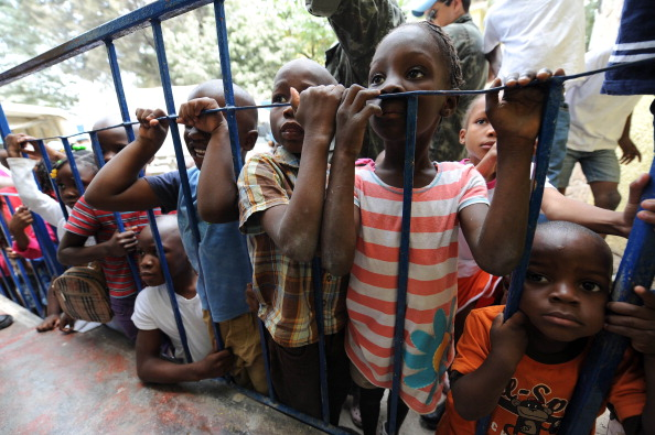 Haitian children orphaned by the 2010 earthquake queue for food given by Brazilian soldiers of the MINUSTAH force at an orphanage in Port-au-Prince (Photo Credit: Vanderlei Almeida/AFP/Getty Images).