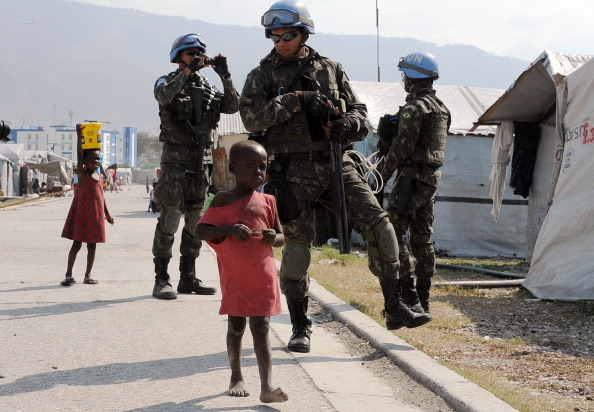 Brazilian soldiers patrol a camp for survivors of the January 2010 quake in Haiti. Hundreds of thousands are still living rough in squalid makeshift camps, and they now face rampant crime, a cholera outbreak and the occasional hurricane (Photo Credit: Vanderlei Almeida/AFP/Getty Images).