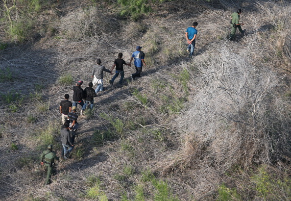 U.S. Border Patrol agents escort a group of undocumented immigrants into custody. (Photo Credit: John Moore/Getty Images)